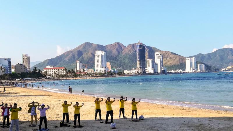 昼のニャチャンビーチで何かをする人々